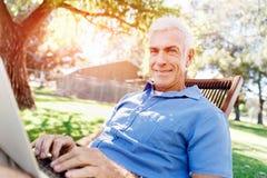 Homme supérieur avec le carnet se reposant en parc Photos libres de droits