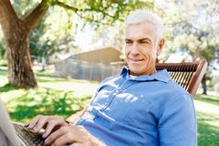 Homme supérieur avec le carnet se reposant en parc Photographie stock libre de droits