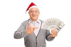 Homme supérieur avec le chapeau de Santa tenant l'argent Images stock
