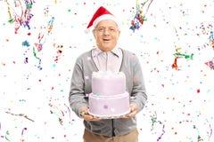 Homme supérieur avec le chapeau de Santa tenant un gâteau Photo libre de droits