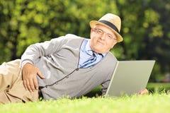 Homme supérieur avec le chapeau se trouvant sur une herbe et travaillant sur un ordinateur portable dedans Photo stock