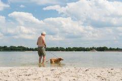 Homme supérieur avec le chien dans l'eau Images stock