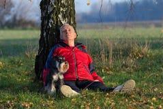 Homme supérieur avec le chien se reposant dans la forêt Image stock