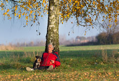 Homme supérieur avec le chien se reposant sur l'herbe se penchant sur l'arbre Photo libre de droits