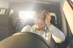 Homme supérieur avec le mal de tête dans la voiture Photographie stock