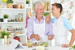 Homme supérieur avec le petit-fils préparant le dîner dans la cuisine Photographie stock libre de droits