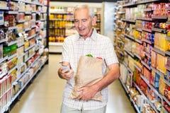 Homme supérieur avec le sac d'épicerie utilisant le smartphone Photographie stock libre de droits