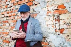 Homme supérieur avec le smartphone contre le mur de briques, textotant Images stock