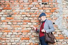 Homme supérieur avec le smartphone contre le mur de briques, textotant Photo libre de droits