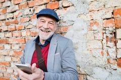 Homme supérieur avec le smartphone contre le mur de briques, textotant Photos libres de droits