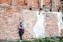 Homme supérieur avec le smartphone contre le mur de briques, textotant Photographie stock libre de droits