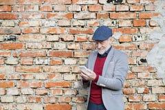 Homme supérieur avec le smartphone contre le mur de briques, textotant Images libres de droits