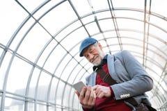 Homme supérieur avec le smartphone contre le service de mini-messages de plafond en verre Images libres de droits