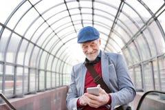 Homme supérieur avec le smartphone contre le service de mini-messages de plafond en verre Photos libres de droits