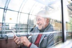 Homme supérieur avec le smartphone contre le service de mini-messages de plafond en verre Images stock