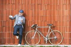 Homme supérieur avec le smartphone et la bicyclette contre le mur de briques Images stock