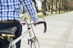Homme supérieur avec le smartphone et la bicyclette en ville Photos libres de droits