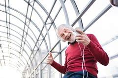 Homme supérieur avec le smartphone et les écouteurs dans le passage Photo stock
