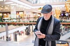 Homme supérieur avec le smartphone faisant des achats de Noël Photographie stock