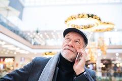 Homme supérieur avec le smartphone faisant des achats de Noël Photos stock
