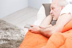 Homme supérieur avec un à télécommande sur un sofa Photo libre de droits