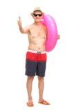 Homme supérieur avec un anneau de natation renonçant à un pouce Images stock