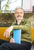 Homme supérieur avec un livre dans l'arrière-cour Photographie stock libre de droits