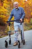 Homme supérieur avec une incapacité de marche appréciant une promenade en parc d'automne Images stock