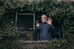 Homme supérieur avec une propriété protectrice d'arme à feu Images libres de droits
