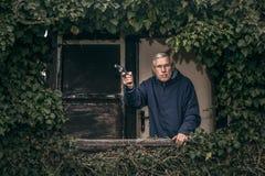 Homme supérieur avec une propriété protectrice d'arme à feu Image stock