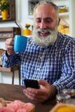 Homme supérieur avec une tasse de thé souriant tout en textotant par l'intermédiaire du smartphon Photos stock