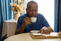 Homme supérieur ayant la boisson tandis que livre de lecture dans la maison de repos Images stock