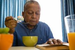 Homme supérieur ayant la nourriture tandis que livre de lecture dans la maison de repos Photo libre de droits
