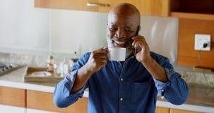 Homme supérieur ayant le café noir tout en parlant au téléphone portable dans la cuisine 4k banque de vidéos