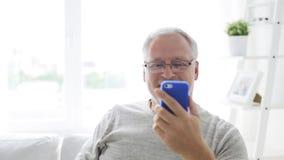 Homme supérieur ayant le faire appel visuel au smartphone à la maison 18 clips vidéos