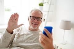 Homme supérieur ayant le faire appel visuel au smartphone à la maison Image libre de droits