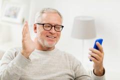 Homme supérieur ayant le faire appel visuel au smartphone à la maison Images libres de droits