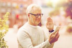Homme supérieur ayant le faire appel visuel au smartphone dans la ville Image libre de droits