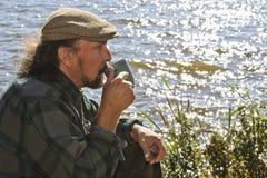 Homme supérieur ayant une boisson chaude par un bord de lac Photographie stock libre de droits