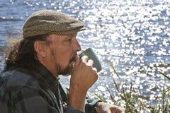 Homme supérieur ayant une boisson chaude par un bord de lac Image libre de droits