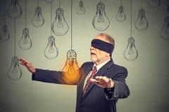 Homme supérieur bandé les yeux marchant par les ampoules recherchant l'idée lumineuse Photographie stock