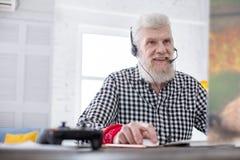 Homme supérieur bel appréciant le jeu vidéo en ligne Image libre de droits