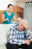 Homme supérieur bouleversé contre l'épouse fâchée Photographie stock libre de droits