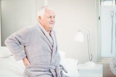 Homme supérieur bouleversé s'asseyant avec douleurs de dos sur le lit Images libres de droits