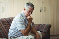 Homme supérieur bouleversé s'asseyant dans le salon Photos libres de droits
