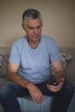 Homme supérieur bouleversé tenant le téléphone portable tout en se reposant sur le sofa Photo libre de droits