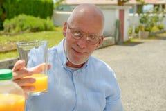 Homme supérieur buvant du jus d'orange dans son jardin Photo stock