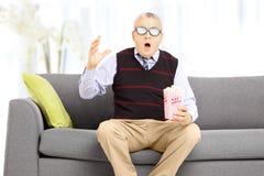 Homme supérieur choqué avec le maïs éclaté se reposant sur le sofa et les mouvements de observation Photographie stock