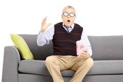 Homme supérieur choqué s'asseyant sur un sofa et un film de observation Photos stock