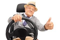 Homme supérieur conduisant et renonçant à un pouce Photographie stock